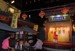 A one-man performance of Peking Opera outside at the Snack Market.