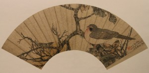 Chinese fan with painting of a bird on a tree.