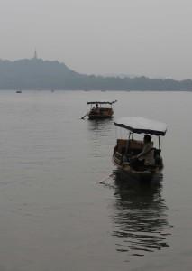 Passenger boats rowing across West lake.