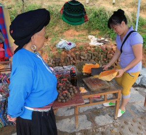 Beehive being diced in to smaller pieces with a local woman in traditional clothing watching.