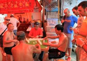 Men playing mahjong in Tai O as western tourists drink beer and observe.