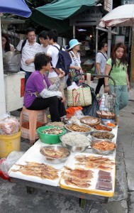 Woman selling various seafood near the village marketplace.