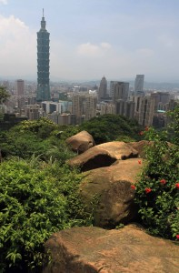 Taipei 101 skyscraper seen from boulders on Elephant Mountain.