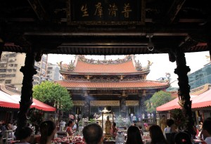 Worshipers and many offerings of sweets and flowers on display before the main hall of Longshan Temple.