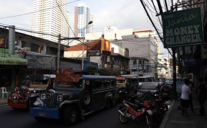 Jeepneys driving down a road in Manila.