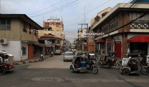 Street in Vigan streaming with traffic – mostly with taxi-motorbikes.
