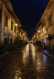 Calle Crisologo after dark and during a light shower.