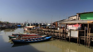 Water taxis docked in the slums with cargo ships docked in Sunda Kelapa Port in the background.