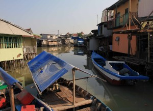 Homes on stilts and boats lining the waterway in the slums.
