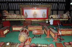 "The ""backstage"" of the shadow puppet theater with musical instruments in view."