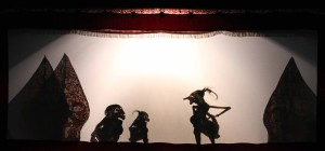 The shadow puppet theater with a character addressing the ape characters.