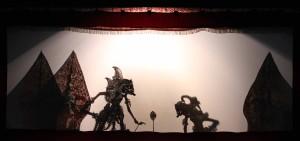 Shadow puppet theater with characters looking at the magical arrow in the play.