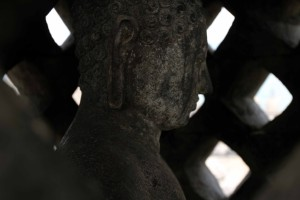 Looking inside one of the completed perforated stupas to see the enclosed Buddha statue.