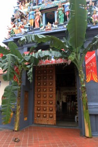 Closeup of the Sri Mariamman Temple entrance with cut banana trees on each side.