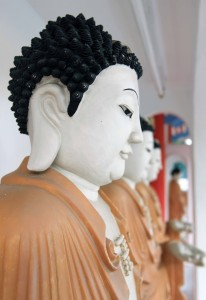 Closeup of Buddha statues that surround the hall.
