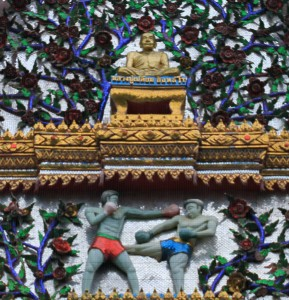 A facade in the monastery with a relief depicting Muay Thai fighters.