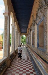 Man walking along the side-hall of the main temple in Siem Reap to open the doors of the temple for me.