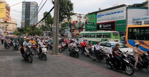 Motorbikes traveling on both the road and sidewalk in Vietnam.