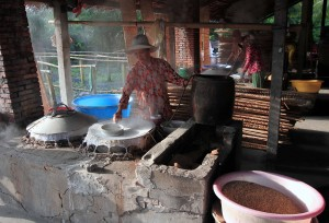 Spreading the rice flour mixture on a cloth stretched out over a fire to cook and congeal it.