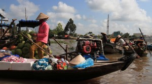 A woman merchant buying goods from another merchant in the Phong Dien floating market.