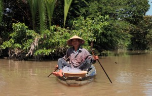 An old man mending a net in his boat.