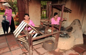 Two women unraveling the silk from boiled cocoons.