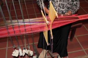 Traditional weaving on a long loom with coral flowers used as weights.
