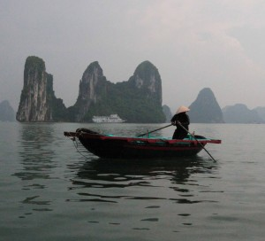 A man rowing his boat in Ha Long Bay.