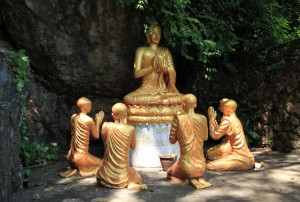 Statues of Buddha and his followers in Wat Tham Phou Si.