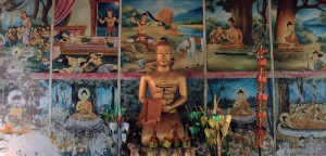 Statue with murals behind it in Wat Tham Phou Si.