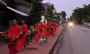 Monks walking along the sidewalk to receive alms early in the morning in Luang Prabang.