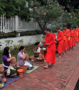 Monks receiving food from the locals during the Alms Ceremony.