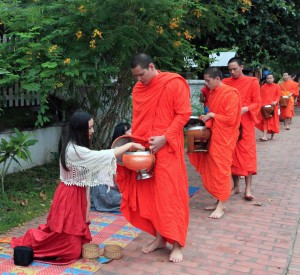 Kneeling woman giving food to a monk during the Alms Ceremony.