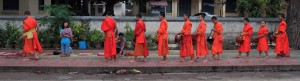 Monks lined up on the sidewalk during the Alms Ceremony.