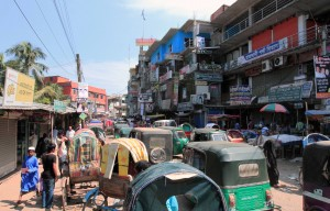 Chaotic street filled with rickshaws and auto-rickshaws in Mograpara.