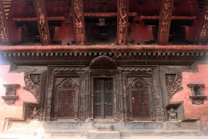 Wood-carved entrance and lattice windows to one oft he temples in the square.