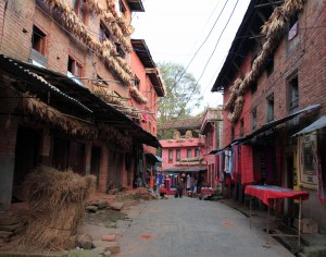 Street to Changu Narayan, with corn hanging from the walls of the buildings.