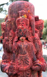 Sculpture (looks like a Shivalinga) with food stuffed in the mouth of the god.