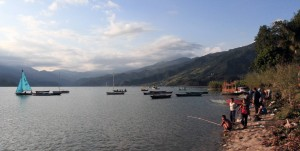 Children fishing on the shore of Phewa Lake.