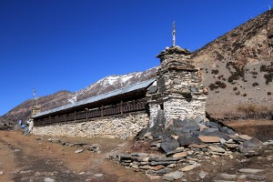 A long prayer wheel wall with Mani stones piled at both ends.