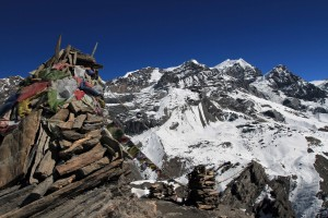 Piles of stones and prayer flags strung up at the viewpoint by Thorung High Camp.