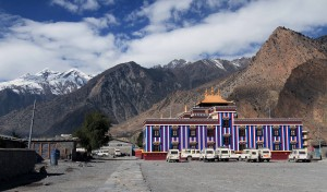 Colorful building in Jomsom with many jeeps parked outside.