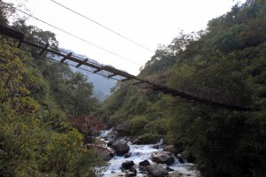 A decommissioned wooden suspension bridge, missing more than a few planks.