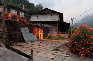 Firelight emanating from a home in Old Ghandruk during dusk.
