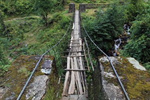 An old wooden suspension bridge, patched up with logs, near Tolka.
