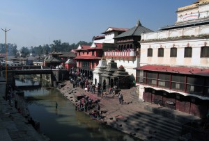 Ill woman on a stretcher, surrounded by helpers, with her feet dipped in to the Bagmati River.