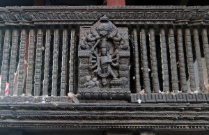 Wood carved railing on one of the temples in the square.