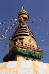 Closeup of the Swayambhunath stupa with the dome, eyes of Buddha, pentagonal torans, thirteen tiers, and an umbrella on top.