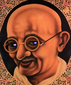 Odd artwork of Gandhi with small television screens for eyes.