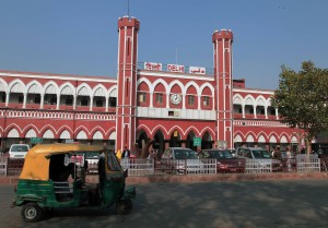 The Delhi Railroad Station with an auto rickshaw parked in front.